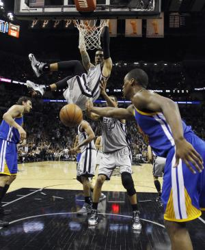 San Antonio Spurs' Danny Green scores over Golden State Warriors' Andrew Bogut, left, and Harrison Barnes (40) during the second half in Game 5 of a Western Conference semifinal NBA basketball playoff series, Tuesday, May 14, 2013, in San Antonio. (AP Photo/Eric Gay)