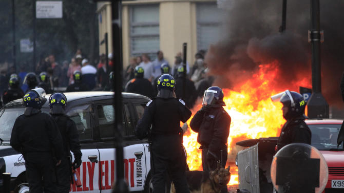 British police officers stand around  as a car, background, burns after it was set on fire by rioters in Hackney, east London, Monday Aug. 8, 2011. Youths set fire to shops and vehicles in a host of areas of London _ which will host next summer's Olympic Games _ and clashed with police in the nation's central city of Birmingham, as authorities struggled to halt groups of rampaging young people.  (AP Photo/Lefteris Pitarakis)