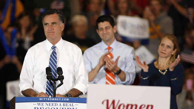 Republican presidential candidate former Massachusetts Gov. Mitt Romney pauses for applause as he speaks as running mate Rep. Paul Ryan, R-Wis., and his wife Janna listen during a campaign rally at the Marion County Fairgrounds in Marion, Ohio, Sunday, Oct. 28, 2012. (AP Photo/Mike Munden)