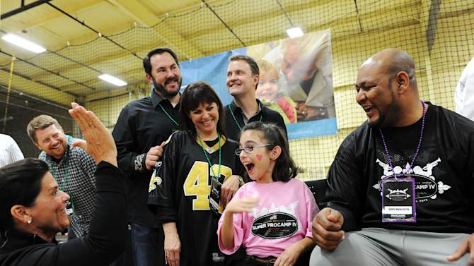 IMAGE DISTRIBUTED FOR STARKEY HEARING FOUNDATION - Tani Austin, co-founder of the Starkey Hearing Foundation, high-fives nine-year-old Maci Rowen who heard for the first time, while sitting next to former Saints player Deuce McAllister after getting fitted with a hearing aid at The Citi Garth Brooks Super Pro Camp on Friday, Feb. 1, 2013 in New Orleans. (Photo by Cheryl Gerber/Invision for Starkey Hearing Foundation/AP Images)
