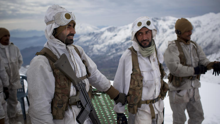 FILE-This Feb. 20, 2012 file photo shows Pakistani Army soldiers with the 20th Lancers Armored Regiment, gather before a patrol atop the 8000 foot mountain near their outpost Kalpani Base in Pakistan's Dir province on the Pakistan-Afghan border. Relations between the two countries have not been good in recent years, with Afghanistan often blaming Pakistan for supporting insurgents that are fighting both NATO troops and government forces. Major attacks and suicide bombings are regularly blamed on Pakistan, playing to a domestic audience that increasingly considers its neighbor responsible for the war.(AP Photo/Anja Niedringhaus, File)