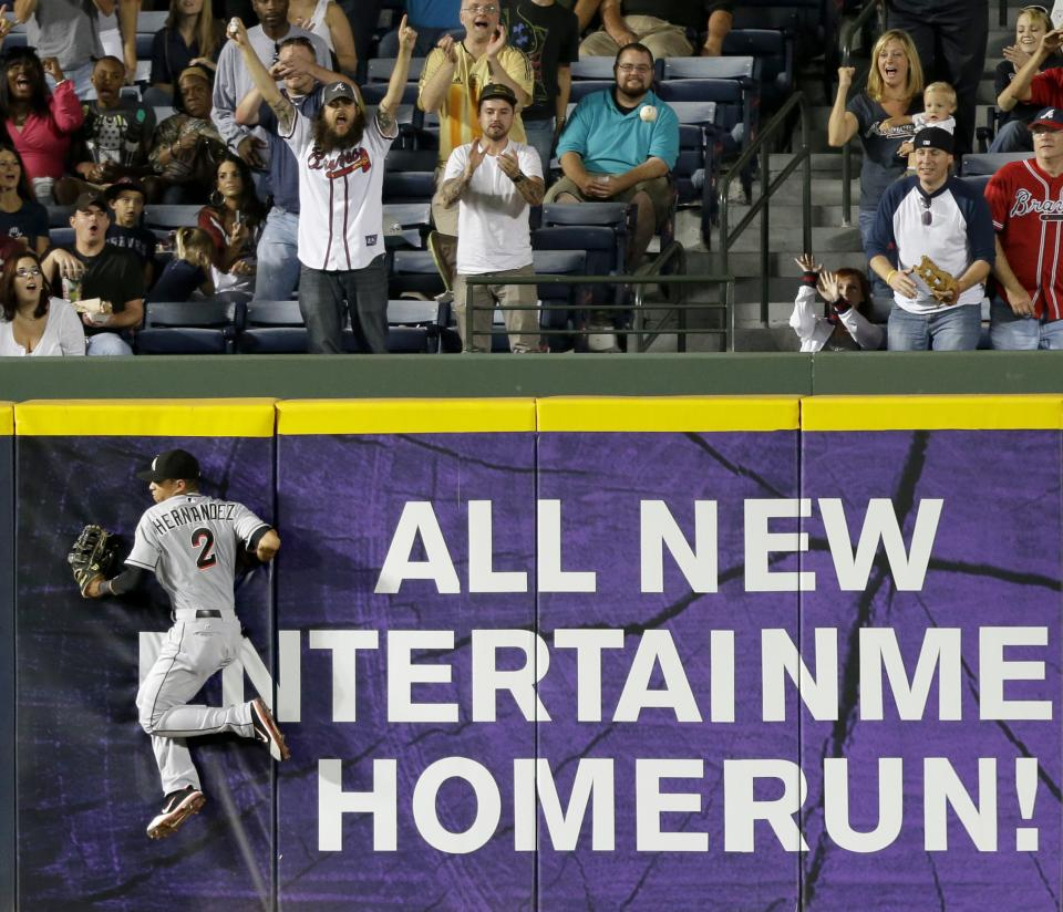 Miami Marlins center fielder Gorkys Hernandez goes up against the wall as he chases down a triple by Atlanta Braves' Jason Heyward during the sixth inning of a baseball game Tuesday, Sept. 25, 2012, in Atlanta. (AP Photo/David Goldman)