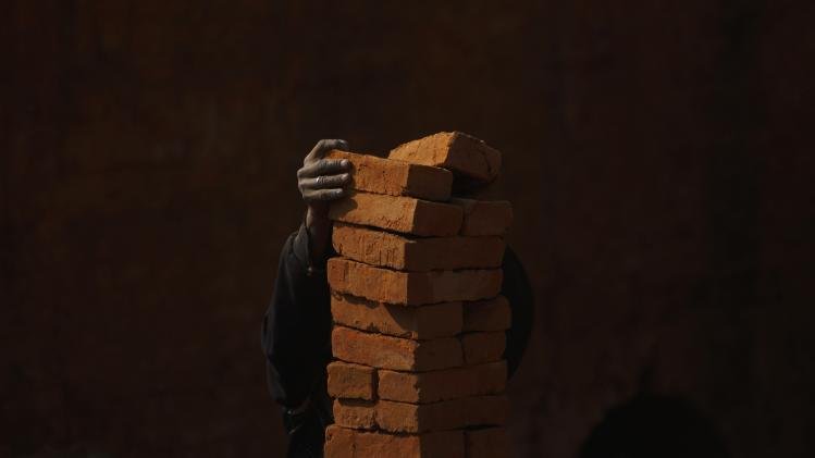 A man stack bricks before carrying them at a brick factory in Lalitpur