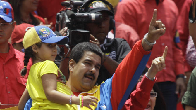 Venezuela's acting President Nicolas Maduro holds a girl in his arms as he gestures to supporters after registering his presidential candidacy to replace late President Hugo Chavez at the national electoral council in Caracas, Venezuela, Monday, March 11, 2013. Presidential elections were announced to take place on April 14, after the death of Chavez on March 5. At right is Attorney General Cilia Flores.  (AP Photo/Fernando Llano)