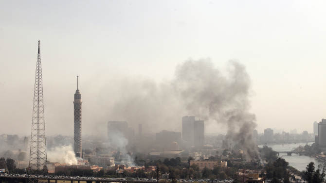 Smoke rises from the Police Officers Club, left, and the Egyptian Soccer Federation, right, after protesters set fire following a court verdict, in Cairo, Egypt, Saturday, March 9, 2013. Fans of Cairo's Al-Ahly club have stormed Egypt's soccer federation headquarters, set it ablaze after a court acquitted seven of nine police official on trial for their alleged part in deadly stadium melee. A fire also broke out Saturday in a nearby police club, but it was not immediately known whether Al-Ahly fans started the blaze there too. (AP Photo/Maya Alleruzzo)