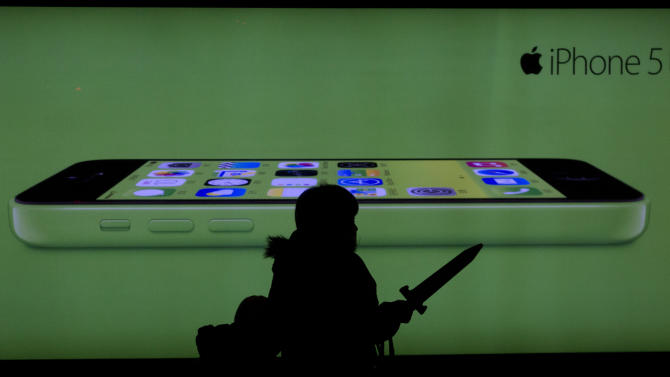 A woman holding a toy sword walks past an advertisement for the iPhone in Beijing Monday, Dec. 16, 2013. Apple Inc. might have a chance to pep up cooling iPhone sales in China if it finally can reach a deal with the world's biggest phone carrier. (AP Photo/Ng Han Guan)