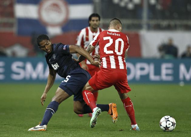 Manchester United's Ferdinand struggles for the ball against Olympiakos' Holebas during their Champions League round of 16 first leg soccer match in Piraeus, near Athens,