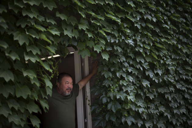 "Artist Ai Weiwei poses for photos at a door of his studio in Beijing, China, Wednesday, May 22, 2013. Ai's music video accompanying his heavy metal single ""Dumbass'' released Wednesday depicts an inse"
