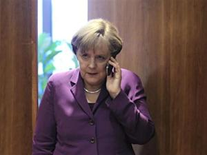 Germany's Chancellor Merkel uses her mobile phone before a meeting at a European Union summit in Brussels