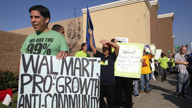 Anthony Degoege protests outside a Walmart store  in Paramount, Calif., Friday Nov. 23, 2012. Wal-Mart employees and union supporters are taking part in today's nationwide demonstration for better pay and benefits A union-backed group called OUR Walmart, which includes former and current workers, staged the demonstrations and walkouts at hundreds of stores on Black Friday, the day when retailers traditionally turn a profit for the year. (AP Photo/Nick Ut)