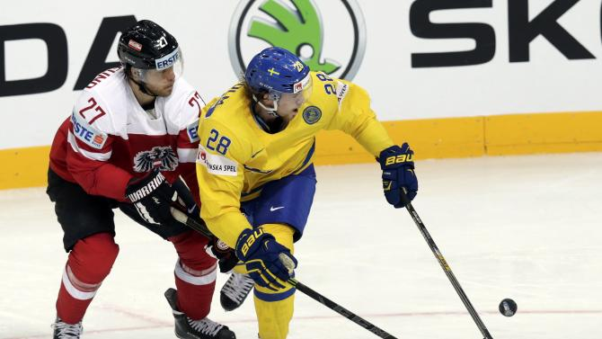 Sweden's Lindholm fights for the puck with Austria's Hundertpfund during their Ice Hockey World Championship game at the O2 arena in Prague