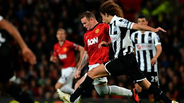 Manchester United's Wayne Rooney (C) vies for the ball with Newcastle United's Fabricio Coloccini (2nd R) during the third round of the League Cup on September 26 2012