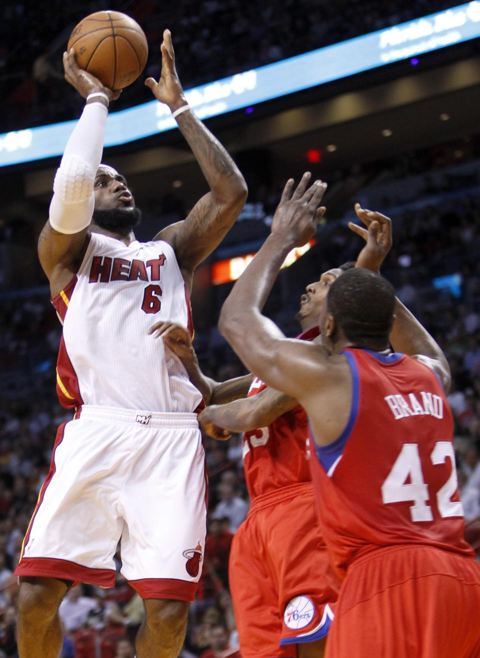 Miami Heat forward LeBron James (6) goes up for a shot against Philadelphia 76ers guard Lou Williams, center, and Philadelphia 76ers forward Elton Brand (42) during the first half of an NBA basketball game, Tuesday, April 3, 2012 in Miami. (AP Photo/Wilfredo Lee)