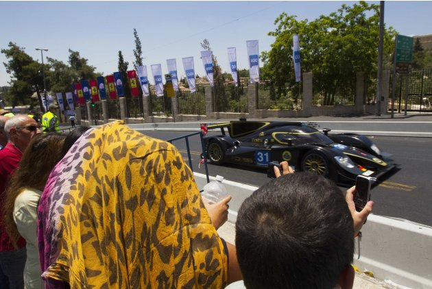 Spectators take photographs of a Lotus during a road show in Jerusalem