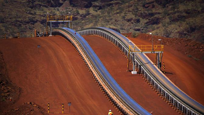 File picture of a worker walking near conveyer belts loaded with iron ore at the Fortescue Solomon iron ore mine located in the Valley of the Kings
