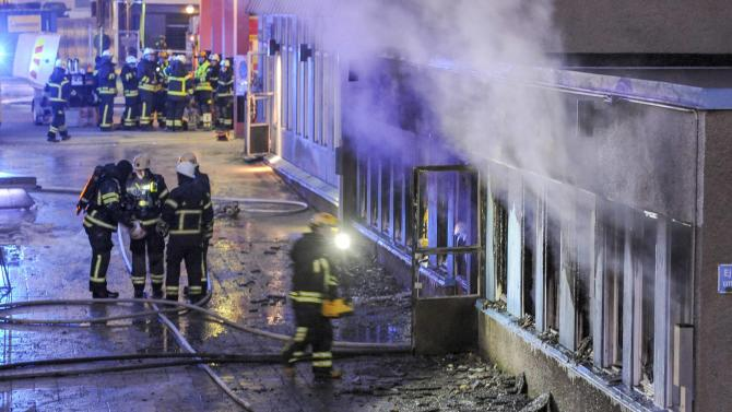 Firemen work as smoke billows from the windows of a mosque in Eskilstuna