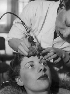 A vintage photo of a women betting her eyebrows shaped