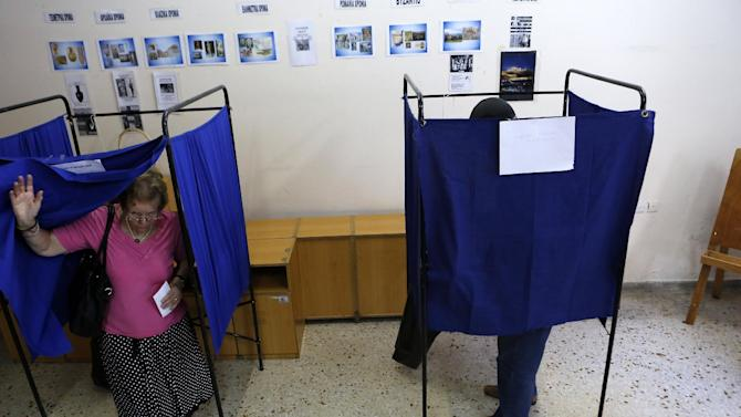 People cast their vote at a polling station in Athens, Sunday, July 5, 2015. Greeks began voting early Sunday in a closely-watched, closely-contested referendum, which the government pits as a choice over whether to defy the country's creditors and push for better repayment terms or essentially accept their terms, but which the opposition and many of the creditors paint as a choice between staying in the euro or leaving it. (AP Photo/Petros Karadjias)