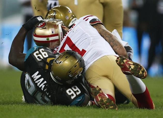 Jacksonville Jaguars defensive tackle Sen'Derrick Marks (99) pulls on the helmet of San Francisco 49ers quarterback Colin Kaepernick during the first half of an NFL football game at Wembley Stadium, L