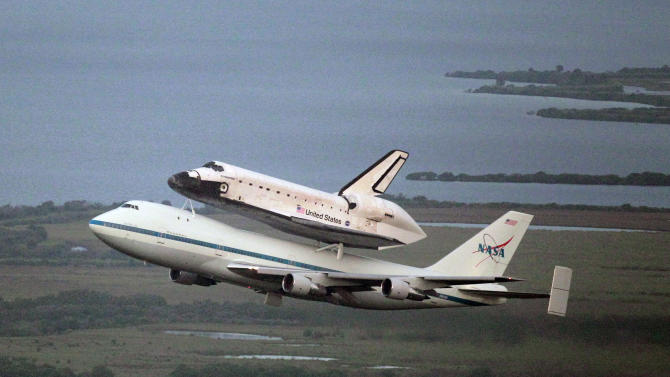 Space shuttle Endeavour, bolted atop a modified jumbo jet, makes its departure from the Kennedy Space Center, Wednesday, Sept. 19, 2012, in Cape Canaveral, Fla. Endeavour will make a stop in Houston before heading to the California Science Center in Los Angeles. (AP Photo/John Raoux)