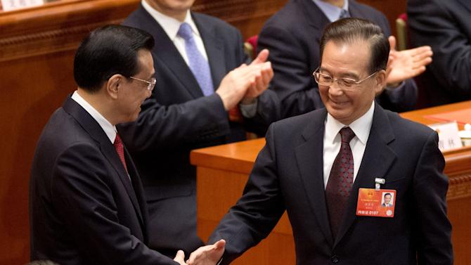 Newly-named Chinese Premier Li Keqiang, left, is greeted by his predecessor Wen Jiabao after delegates voted Li as the new premier during a plenary session of the National People's Congress at the Great Hall of the People in Beijing Friday, March 15, 2013. China named the Communist Party's No. 2 leader, Li, premier on Friday as a long-orchestrated leadership transition nears its end, leaving the new leaders to confront uneven economic growth, unbridled corruption and a severely befouled environment that are stirring public discontent. (AP Photo/Andy Wong)