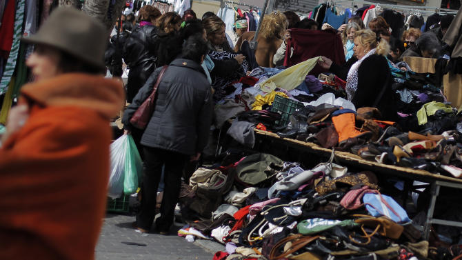 People look at second hand items for sale at a street market in Madrid, Sunday, March 3, 2013. Spain's Prime Minister Mariano Rajoy has conceded that the government just failed to reduce its budget deficit in 2012 to the level it promised European authorities. Rajoy said the deficit fell to 6.7 percent of the country's annual gross domestic product from 9 percent in 2011. (AP Photo/Andres Kudacki)