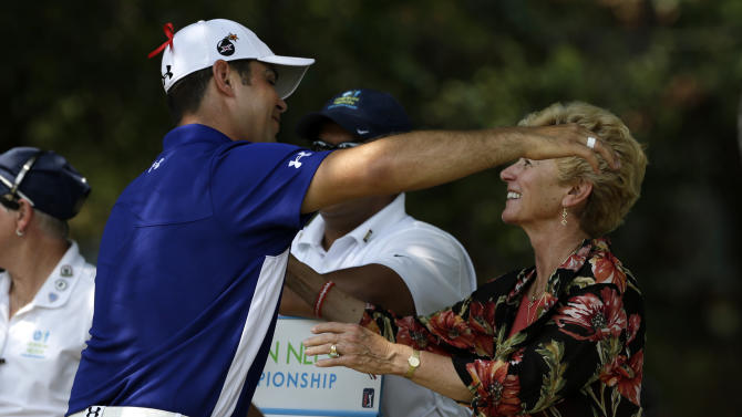Gary Woodland, left, embraces Peggy Nelson, widow of tournament namesake Byron Nelson, before Woodland teed off on the final round of the golf tournament on Sunday, May 19, 2013, in Irving, Texas. (AP Photo/Tony Gutierrez)