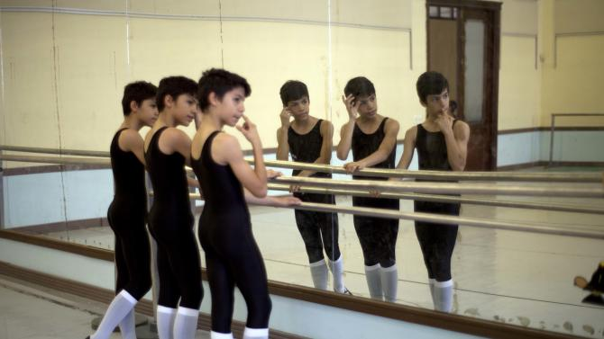 """In this April 3, 2013 photo, identical triplets Marcos, Cesar and Angel Ramirez Castellanos stand at the bar at the start of ballet class at the National School of Ballet in Havana, Cuba. The triplets say they fell in love with dance in 2007 when their mother took them to see a performance of """"The Nutcracker,"""" which is put on every Christmas season and costs just pennies to attend. (AP Photo/Ramon Espinosa)"""
