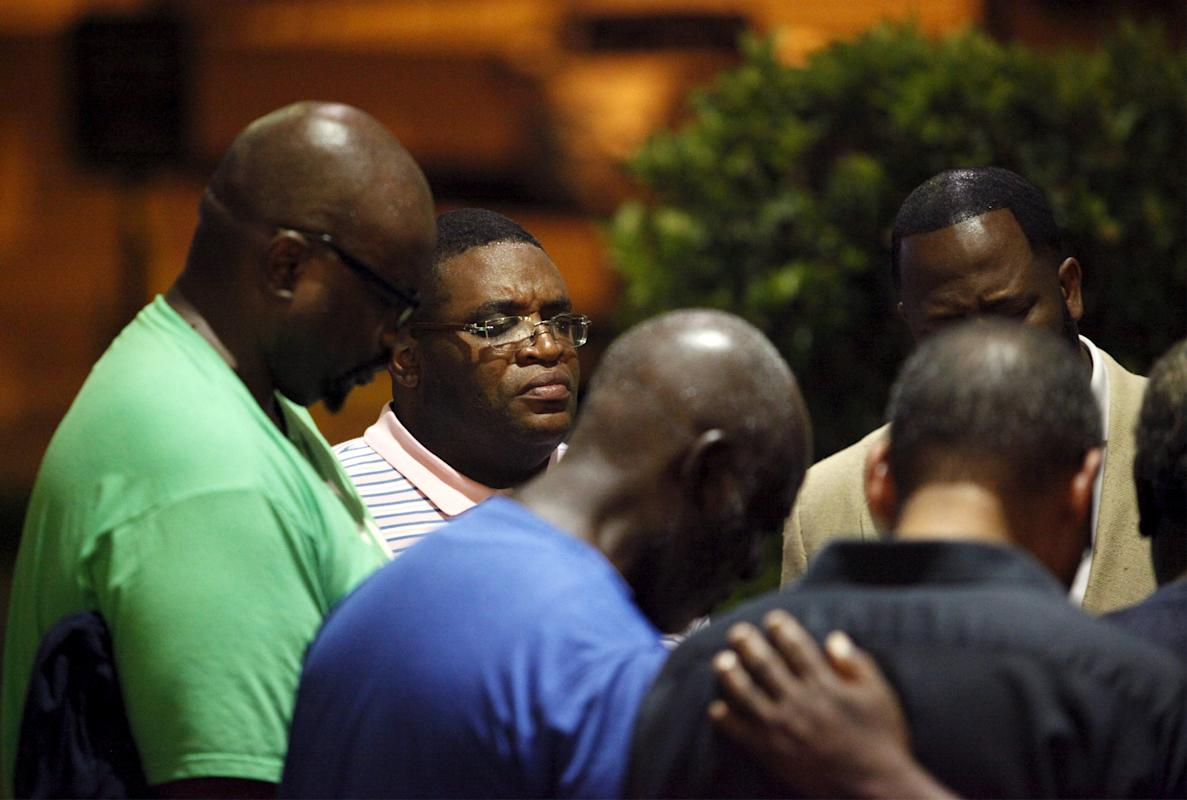 A small prayer circle forms nearby where police are responding to a shooting at the Emanuel AME Church in Charleston