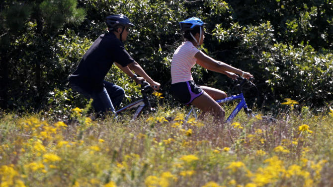 President Barack Obama, left, and his daughter Malia Obama, right, ride bicycles in Manuel F. Correllus State Forest, in West Tisbury, Mass., on the island of Martha's Vineyard, Tuesday, Aug. 23, 2011.  (AP Photo/Steven Senne)