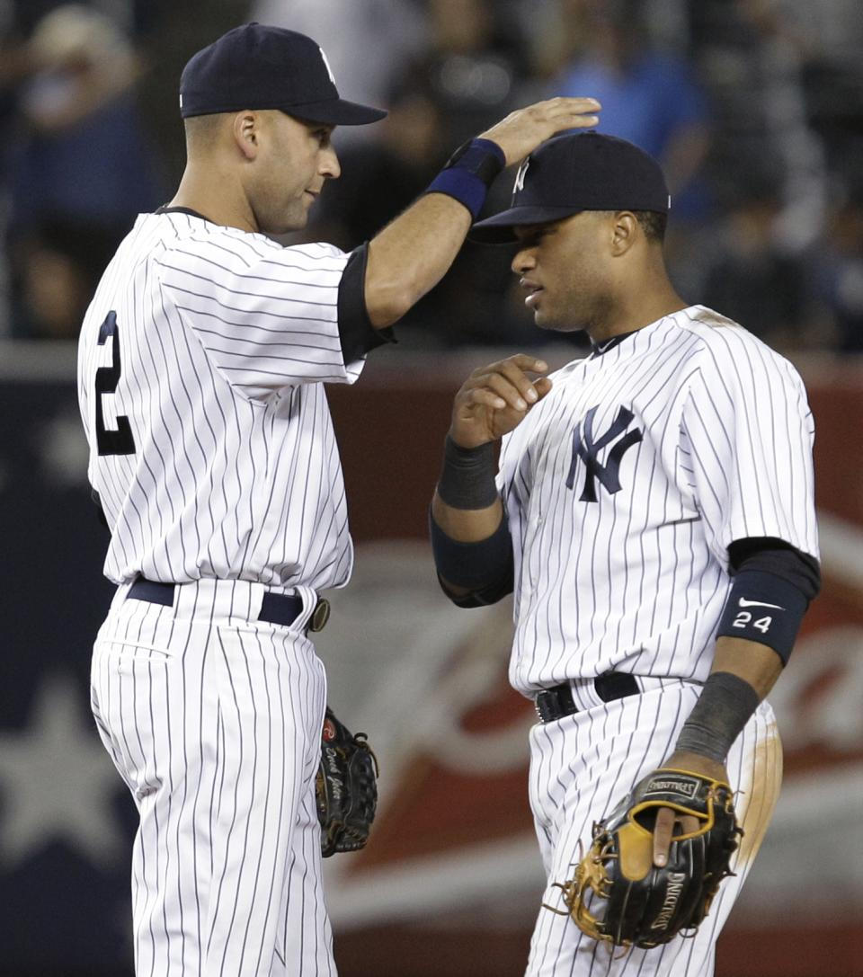 New York Yankees shortstop Derek Jeter (2) taps New York Yankees second baseman Robinson Cano on the cap after the Yankees' 7-1 victory over the Cleveland Indians in a baseball game at Yankee Stadium in New York, Monday, June 25, 2012. Cano had two home runs in the game. (AP Photo/Kathy Willens)