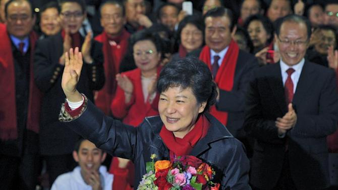 South Korea's presidential candidate Park Geun-Hye of ruling Saenuri Party, waves to supporters after arriving at the party headquarters in Seoul, South Korea, on Wednesday Dec. 19, 2012.   Liberal South Korean candidate has conceded victory to Park Geun-Hye.  Following her election victory Park Geun-hye will return to her childhood home, the presidential palace from where her dictator father President Park Chung-hee ruled South Korea for 18-years. (AP Photo / KIM JAE-HWAN, pool)