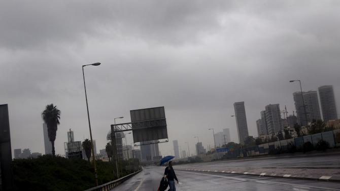 A person crosses the blocked and flooded Ayalon freeway in Tel Aviv, Israel,Tuesday, Jan. 8, 2013. Heavy rains flooded Tel Aviv. (AP Photo/Ariel Schalit)