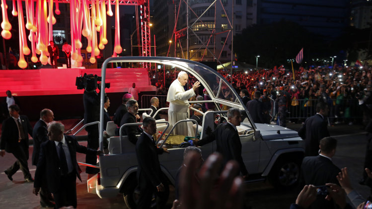 Pope Francis waves to pilgrims as he passes by the 13th station of the cross, top left, during a Stations of the Cross event, among the most popular and solemn Catholic rituals, along Copacabana beach in Rio de Janeiro, Friday, July 26, 2013. Also known as the Way of the Cross, Via Crucis and Via Dolorosa, the Stations of the Cross are built around reflections on Jesus' last steps leading up to his crucifixion and death. (AP Photo/Enric Marti)