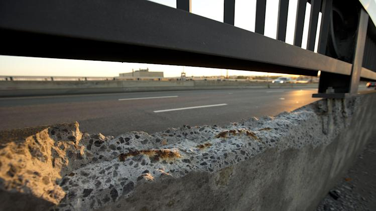 "Cracked concrete exposes parts of reinforcement bars on the Frederick Douglass Memorial Bridge which spans the Anacostia River in Washington on Wednesday, Sept. 4, 2013. The bridge, which carries more than 70,000 vehicles a day, was designed to last 50 years. It's now 13 years past its life expectancy. An Associated Press analysis of 607,380 bridges in the most recent federal National Bridge Inventory showed that 65,605 were classified as ""structurally deficient"" and 20,808 as ""fracture critical,"" making them higher risk bridges. (AP Photo/Alex Brandon)"
