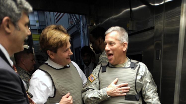Benet Laboratories mechanical engineer Victor Nerses, left, Michigan State Sen. Steven Bieda, and Lt. General Raymond V. Mason, U.S. Army Deputy Chief, share a laugh as Bieda and Mason try on individual cooling vests worn by Abrams Battle Tank crew members to keep them cool, Wednesday, April 11, 2012 in Warren, Mich. The U.S. Army unveiled a new laboratory Wednesday that can simulate Afghanistan's desert heat and Antarctica's extreme cold in an effort to discover how to save energy and make combat vehicles fuel-efficient. (AP Photo/Detroit News, Todd McInturf )  DETROIT FREE PRESS OUT; HUFFINGTON POST OUT