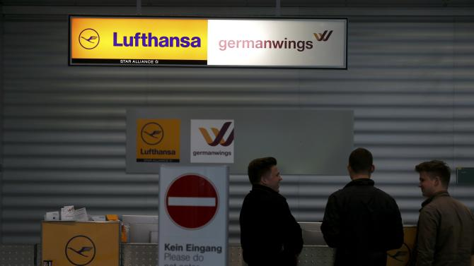 Passengers wait at a check-in counter of German airlines Lufthansa and Germanwings at Duesseldorf airport