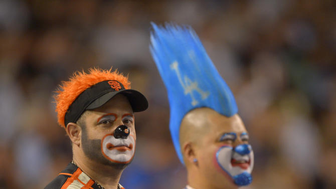 A San Francisco Giants, fan, left, and a Los Angeles Dodgers fan watch the two teams play in their baseball game, Tuesday, June 25, 2013, in Los Angeles. (AP Photo/Mark J. Terrill)