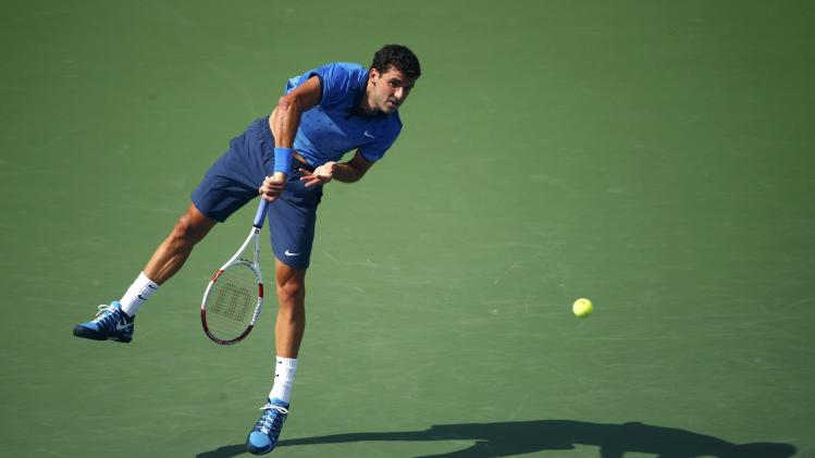 Dimitrov of Bulgaria serves to Monfils of France during their fourth round match at the 2014 U.S. Open tennis tournament in New York