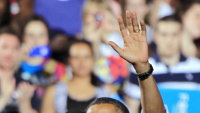 President Barack Obama waves with first lady Michelle Obama after a campaign rally at The Ohio State University in Columbus, Ohio, Saturday, May 5, 2012. (AP Photo/Mark Duncan)