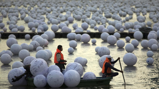 "Workers arrange ""wishing spheres"" as part of an art installation on the Singapore River"