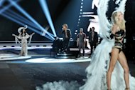 Singer Bruno Mars, center, performs while a modesl walk the runway during the 2012 Victoria's Secret Fashion Show on Wednesday Nov. 7, 2012 in New York. The show will be Broadcast on Tuesday, Dec. 4 (10:00 PM, ET/PT) on CBS. (Photo by Evan Agostini/Invision/AP)