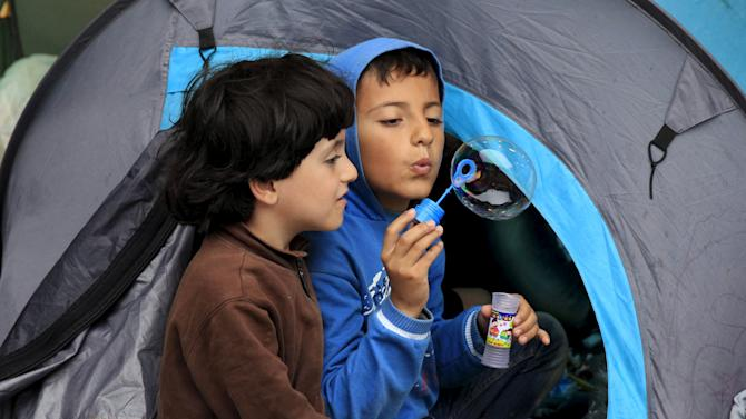 Children of a migrant blow soap bubble at makeshift camp at an underground station in front of Keleti railway station in Budapest