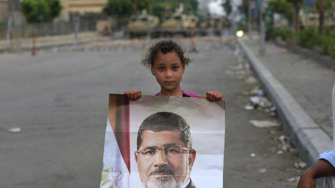 "A supporter of ousted Egypt's President Mohammed Morsi poses with his photo as army soldiers guard at the Republican Guard building in Nasr City, in Cairo, Egypt, Wednesday, July 10, 2013. After days of deadlock, Egypt's military-backed interim president named a veteran economist as prime minister on Tuesday and appointed pro-democracy leader Mohamed ElBaradei as a vice president, while the army showed its strong hand in shepherding the process, warning political factions against ""maneuvering"" that impedes the transition(AP Photo/Hassan Ammar)"