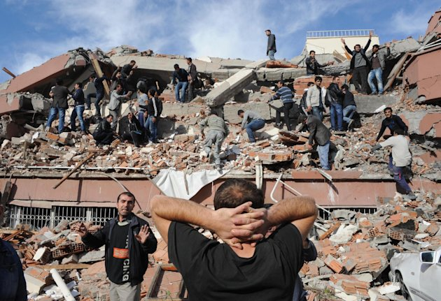 People try to save people trapped  under debris in Tabanli village near the city of Van after a powerful earthquake struck eastern Turkey Sunday Oct. 23, 2011, collapsing some buildings and causing a