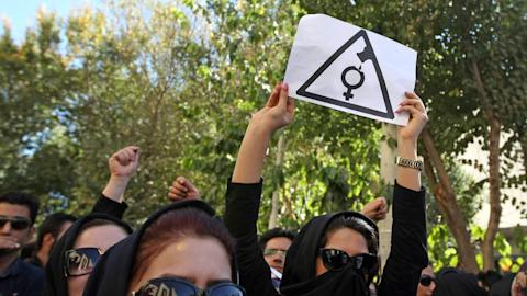 Iranian women, hiding their faces so as not to be identified, shout slogans during a protest in front of the judiciary building on October 22, 2014 in Isfahan, in solidarity with women injured in a series of acid attacks