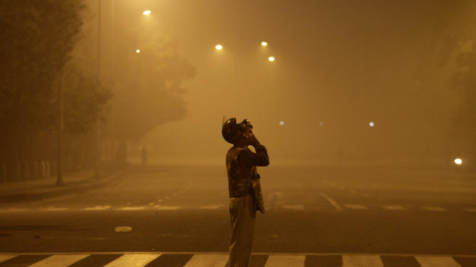 An Indian policeman walks back after chasing away protestors during a violent protest in New Delhi, India, Sunday, Dec. 23, 2012. Police in India's capital used tear gas and water cannons for a second day Sunday in a high-security zone to break up protests by thousands of people demonstrating against the gang rape and beating of a 23-year-old student on a bus.(AP Photo/Altaf Qadri)