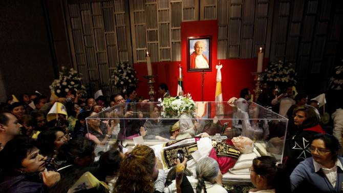 People stand around a glass case containing a wax figure of Pope John Paul II with relics and a vial of the ex-pontiff's blood at the Basilica of Guadalupe in Mexico City, Thursday Aug. 25  2011.  Relics of Pope John Paul II have arrived for public display in Mexico City for a four-month tour of the country. Mexico was the third most visited country by the pope, behind his homeland of Poland and France. He died in 2005 at the age of 84. He was beatified in May.  (AP Photo/Eduardo Verdugo)