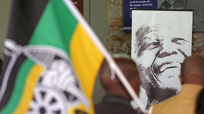 A photo of former South African president Nelson Mandela, right, during a remembrance ceremony in Qunu, South Africa, Saturday, Dec. 7, 2013. Nelson Mandela, 95, anti-apartheid icon and former South African president, has died. The Nobel Peace Prize winner's death was announced by South African President Jacob Zuma on Thursday.(AP Photo/Schalk van Zuydam)