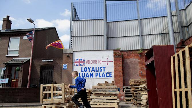 In this photo taken on June 10, 2013,  a boy plays at a bonfire site beside a peace wall that divides the Protestant Cluan Place from the Catholic Short Strand area,  in the Protestant Cluan Place area of East Belfast, Northern Ireland. When President Obama comes to Belfast, he's expected to praise a country at peace and call for walls that separate Irish Catholics and British Protestants to come tumbling down. Barely a 10-minute walk from where the U.S. leader is speaking Monday, June 17, 2013, those walls have kept growing in size and number throughout two decades of slow-blooming peace. Residents on both sides of the battlements today insist they must stay to keep violence at bay.  (AP Photo/Peter Morrison)